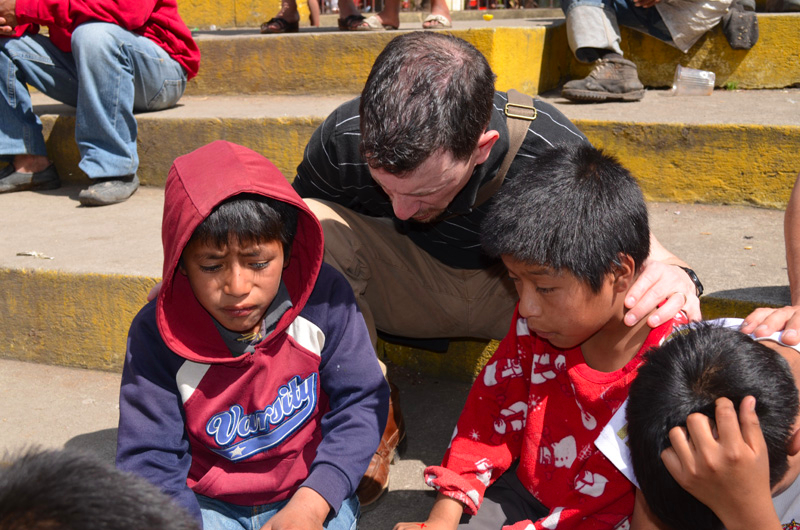 Praying with shoeshine boys